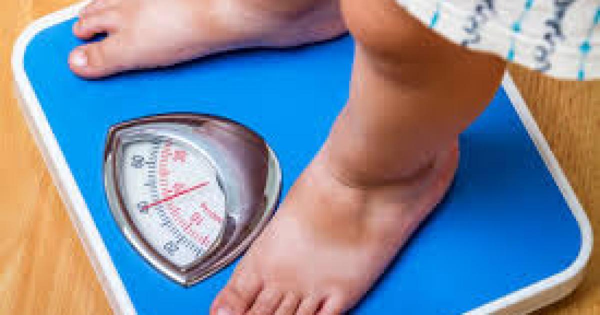 Femeia ține solzi pe fundal galben. scădere în greutate - Imagine de stoc
